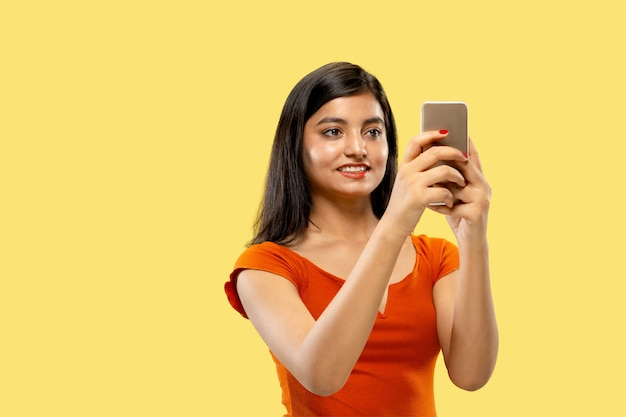 Beautiful female half-length portrait isolated on yellow  space. young emotional indian woman in dress making selfie. negative space