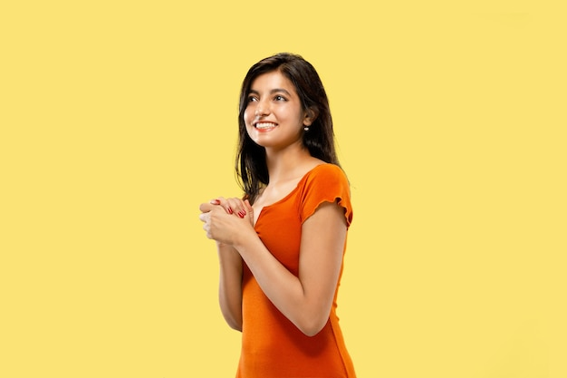 Beautiful female half-length portrait isolated on yellow studio background. young emotional indian woman in dress astonished and happy. negative space. facial expression, human emotions concept.