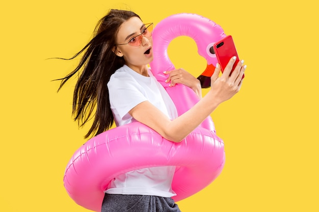 Beautiful female half-length portrait isolated on yellow wall. young smiling woman in red sunglasses making selfie. facial expression, summer, weekend, resort concept. trendy colors.