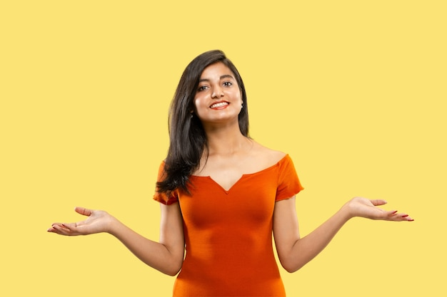 Beautiful female half-length portrait isolated. young emotional indian woman in dress pointing and showing. negative space. facial expression, human emotions concept.