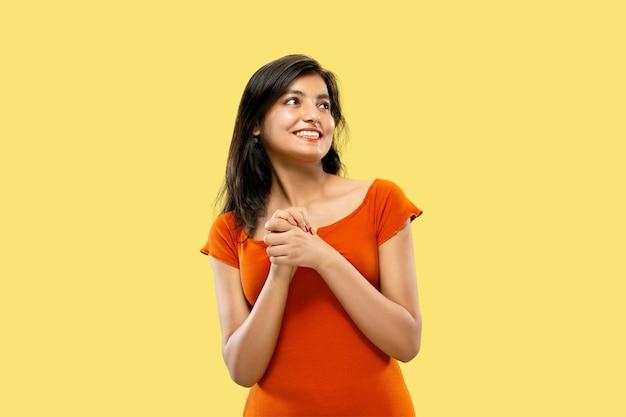 孤立した美しい女性の半分の長さの肖像画。ドレスを着た若い感情的なインドの女性は驚いて幸せです。ネガティブスペース。顔の表情、人間の感情の概念。