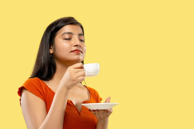 孤立した美しい女性の半分の長さの肖像画。コーヒーを飲むドレスを着た若い感情的なインドの女性。ネガティブスペース。顔の表情、人間の感情の概念。