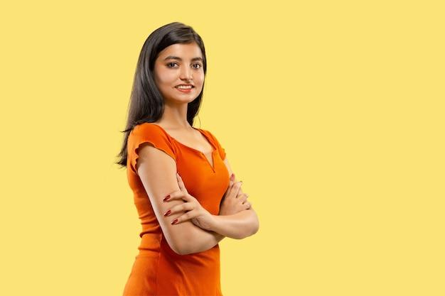 孤立した美しい女性の半分の長さの肖像画。手を交差して立っているドレスを着た若い感情的なインドの女性。ネガティブスペース。顔の表情、人間の感情の概念。