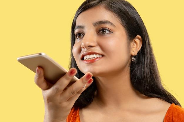 孤立した美しい女性の半分の長さの肖像画。電話で話しているドレスを着た若い感情的なインドの女性。ネガティブスペース。顔の表情、人間の感情の概念。