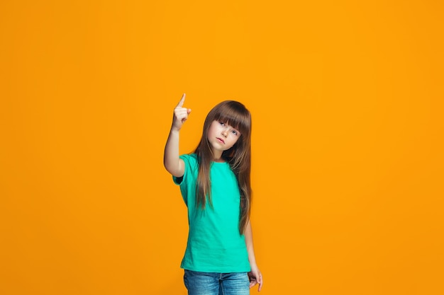 オレンジスタジオ背景に美しい女性の半身像。感情的な十代の少女