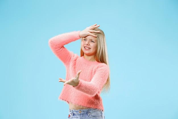 Bellissimo ritratto femminile a mezzo busto su sfondo blu alla moda per studio. giovane ragazza teenager sorpresa, frustrata e sconcertata emotiva.