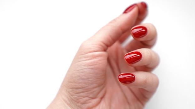Красивая женская рука со свежим красным маникюром и гвоздем, изолированным на белом