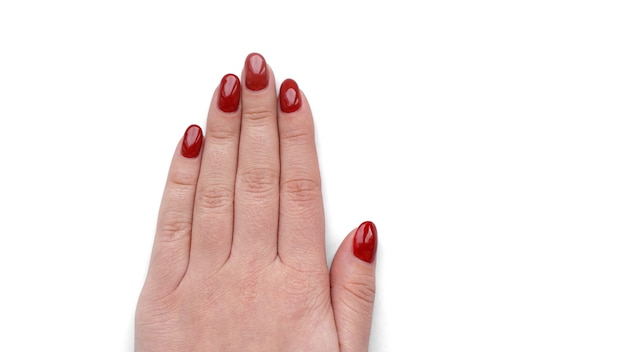 Beautiful female hand with fresh red manicure and nail isolated on white background