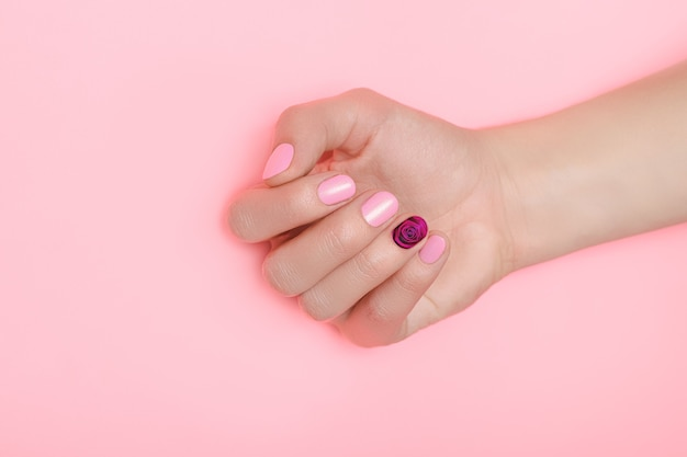 Beautiful female hand with perfect pink nails polish with rose flower nail art on pink surface.