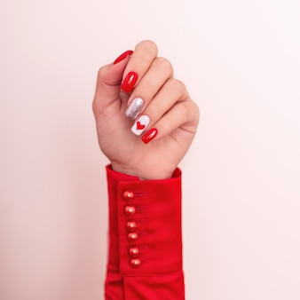 Beautiful female hand with red manicure nails heart and valentines day design