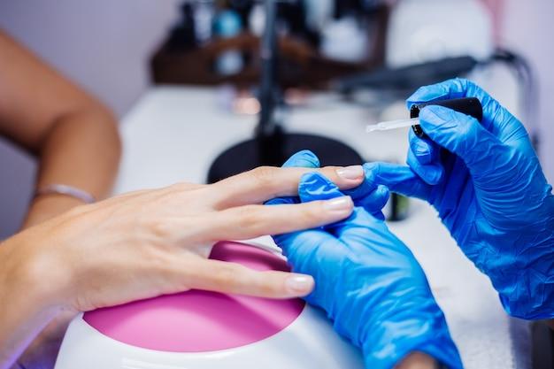 Belle mani femminili processo di fabbricazione di trattamento delle unghie delle dita trapano lima professionale per unghie in azione concetto di cura delle mani e di bellezza