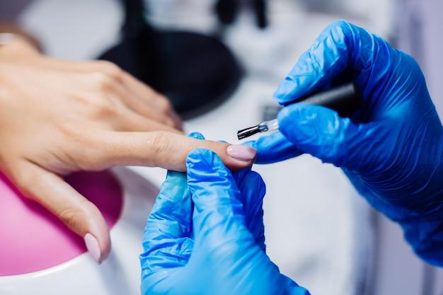 美しい女性の手指の爪の治療プロセスプロのネイルファイルドリルの動作美容とハンドケアのコンセプト