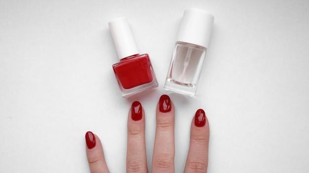 美しい女性の手。ハンドスキンケア。赤いマニキュアと美しい女性の手。赤いマニキュアとキューティクルオイル。