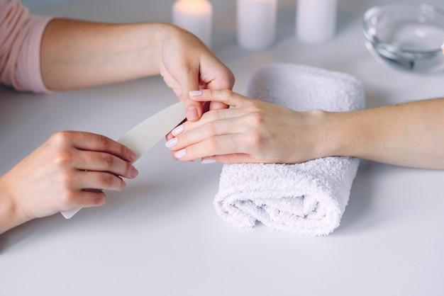 미용실에서 스파 매니큐어 데 아름 다운 여성의 손. 네일 파일을 사용하여 손톱을 닦습니다.