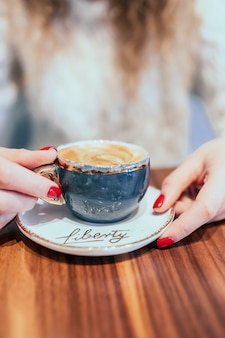 コーヒーカプチーノの灰色のカップを保持している美しい女性の手