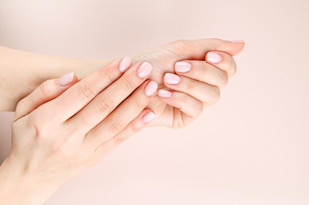 ベージュ色の背景に美しい女性の手