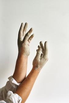 灰色の粘土に塗られた明るい背景の美しい女性の手