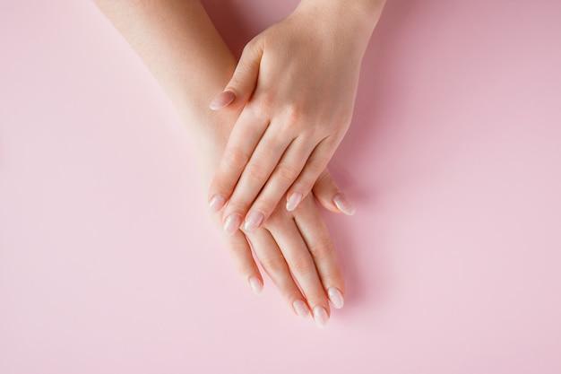 분홍색 배경에 아름다운 여성의 손. 스파 및 바디 케어 개념입니다. 광고용 이미지입니다.