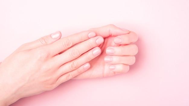 Красивые женские руки, показывающие свежий милый маникюр, концепцию ухода за кожей и ногтями, розовую поверхность