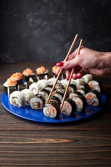 Beautiful female hands take sushi with chopsticks.