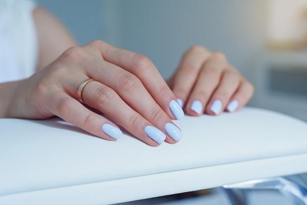 Красивые женские руки с нежным синим маникюром на стенде в салоне красоты