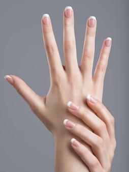 Belle mani femminili con french manicure sulle unghie