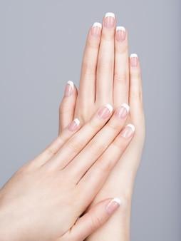 Красивые женские руки с французским маникюром на ногтях