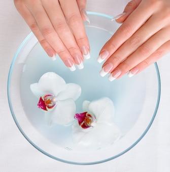 Belle mani femminili con il manicure francese che prepara per ottenere la procedura della stazione termale