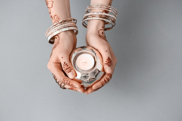 Beautiful female hands with henna tattoo and candle on grey
