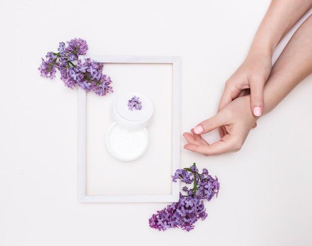 흰색 바탕에 라일락 꽃과 흰색 나무 프레임이 있는 아름다운 여성의 손, 위쪽 전망. 프레임에 핸드 크림입니다. 스킨 케어, 스파의 개념입니다.
