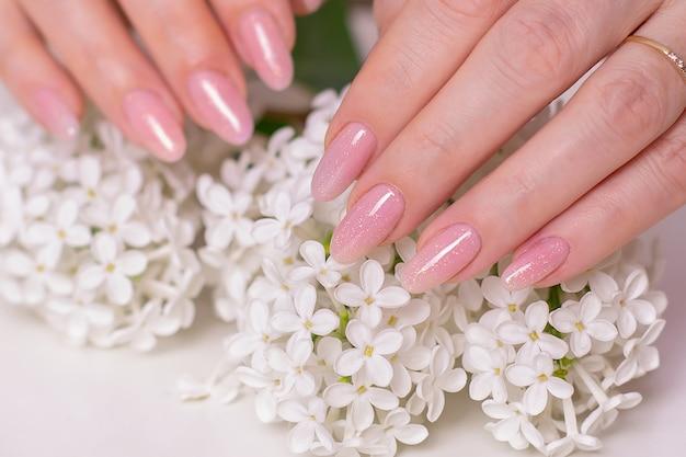 マニキュアネイルピンクジェルポリッシュと白い花と美しい女性の手