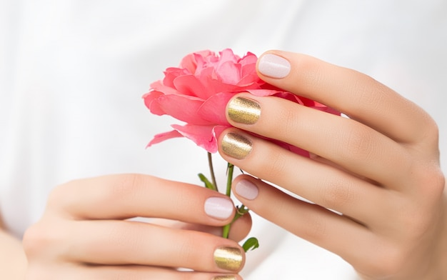 Beautiful female hands with perfect golden and pink nail design hold fresh rose flower