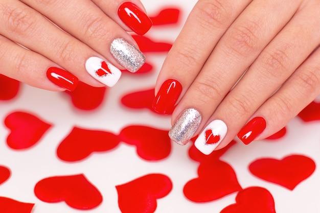 赤いマニキュアの爪、ハート、バレンタインデーのデザインの美しい女性の手