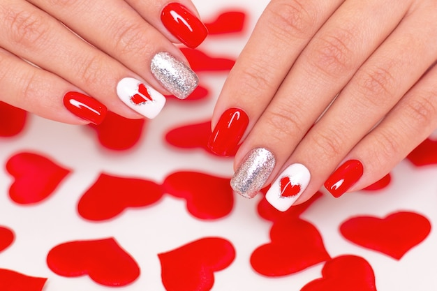 Beautiful female hands with red manicure nails, hearts and valentine's day design