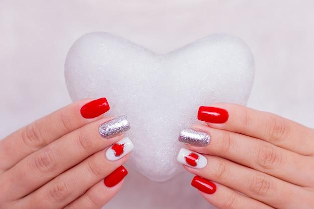Красивые женские руки с красными маникюрными ногтями, держащие ледяное сердце