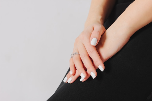 Beautiful female hands with white manicure and engagement ring