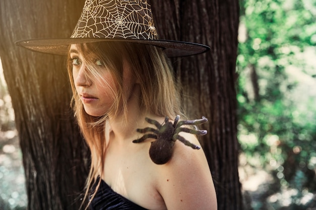 Beautiful female in hat with decorative spider on shoulder looking at camera