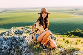 Beautiful female hiker posing on rock