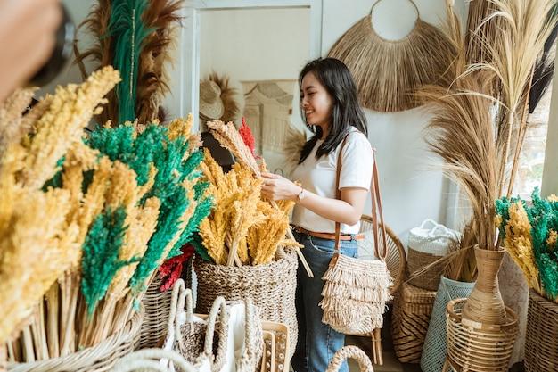 Красивая женщина держит цветочные поделки в ремесленном магазине