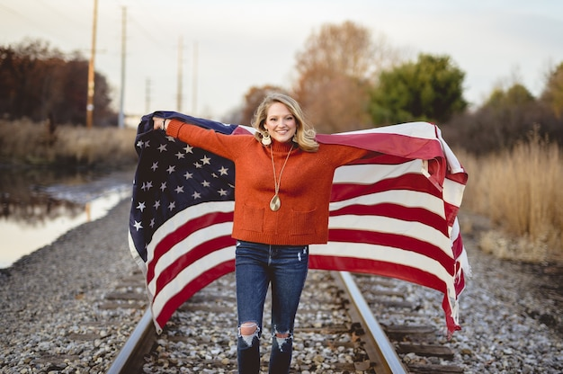 Beautiful female holding the american flag while standing on railway