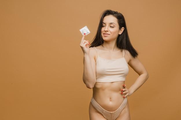 美しい女性はコンドームを保持し、若くて下着でポーズをとる体にフィットします