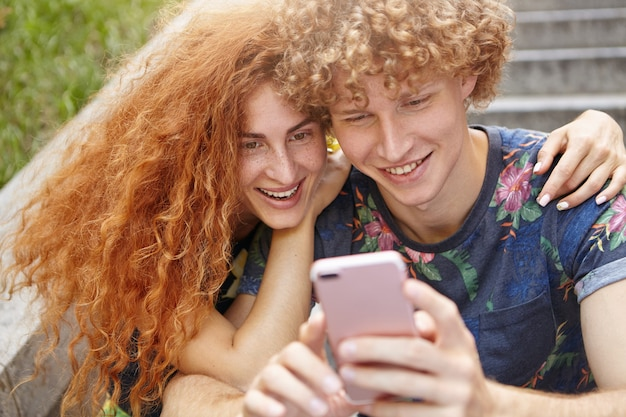 Beautiful female hugging her boyfriend while watching their photos on mobile phone