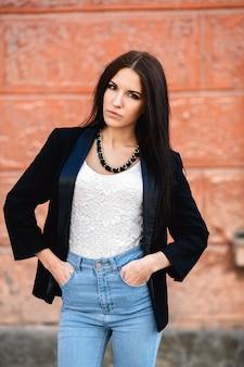 壁のそばのジャケットの美しい女性