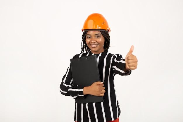 白い壁にフォルダーと建設用ヘルメットの美しい女性