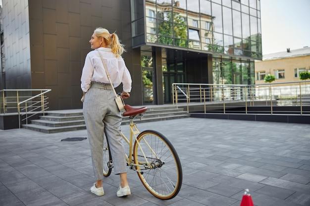 화창한 날 빈 도시 거리에서 복고풍 자전거와 함께 걷는 흰 블라우스와 회색 바지를 입은 아름다운 여성