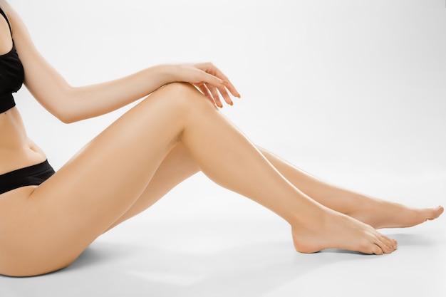 아름 다운 여성의 다리와 배꼽 흰색 배경에 고립. 미용, 화장품, 스파, 제모, 치료 및 피트니스 개념.