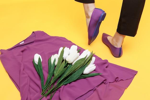 아름다운 여성의 다리는 세련된 보라색 플랫 슈즈를 입고 있습니다.