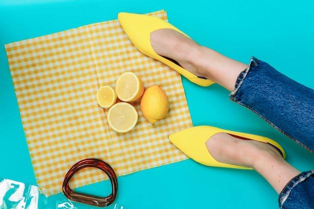 아름다운 여성의 다리는 발 뒤꿈치가없는 세련된 노란색 신발을 입고 있습니다.