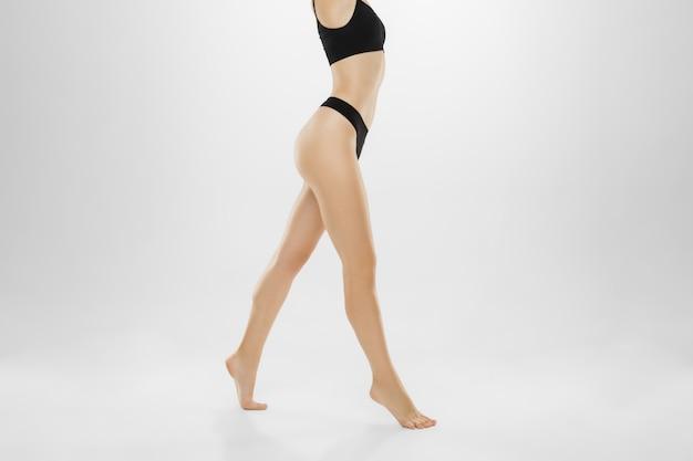 Belle gambe e pancia femminili isolate su bianco.