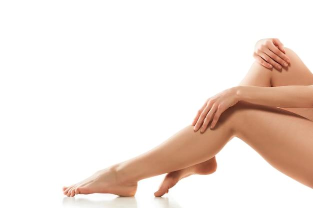 白い壁に隔離された美しい女性の脚、お尻と腹。美容、化粧品、スパ、脱毛、トリートメント、フィットネスのコンセプト。下着の手入れの行き届いた肌で、フィット感とスポーティーで官能的なボディ。